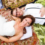 bride and groom laying on picnic blanket tapestries